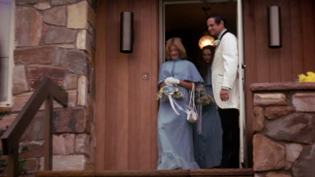 vídeos de stock e filmes b-roll de 1974 wide shot bridesmaids carrying bouquets leaving house / man in tuxedo standing in doorway - 1974