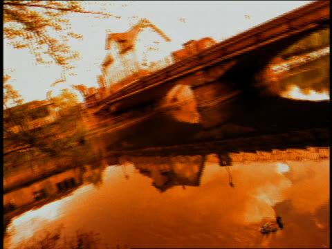 vídeos de stock e filmes b-roll de wide shot bridge and river with ducks / town in background / munich, germany (flash frames) - super exposto