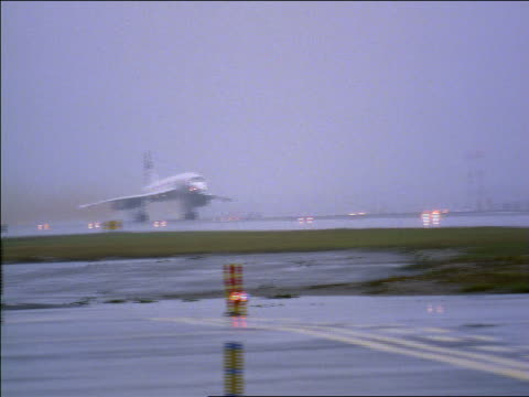 wide shot PAN British Airways Concorde jet taking off from airport on rainy day