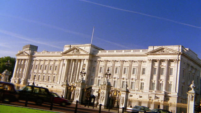 wide shot buckingham palace with traffic in foreground / london - バッキンガム宮殿点の映像素材/bロール