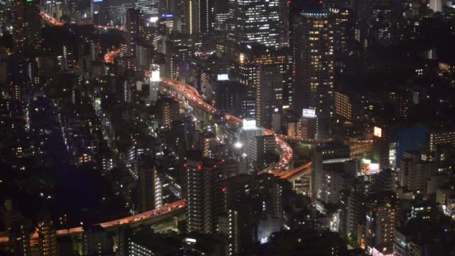 Wide shot buildings and highways are illuminated at night in Tokyo Wide shot cranes operate on a building under construction as the Tokyo Skytree...