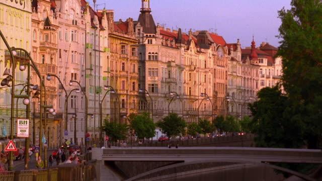 wide shot buildings and people on street / prague, czech republic - praga video stock e b–roll