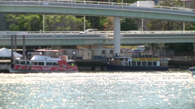 stockvideo's en b-roll-footage met wide shot buildings standing near overpasses and a river in brisbane australia on thursday nov 13 out of focus to in focus shot as a boat passes on a... - passagiersboot