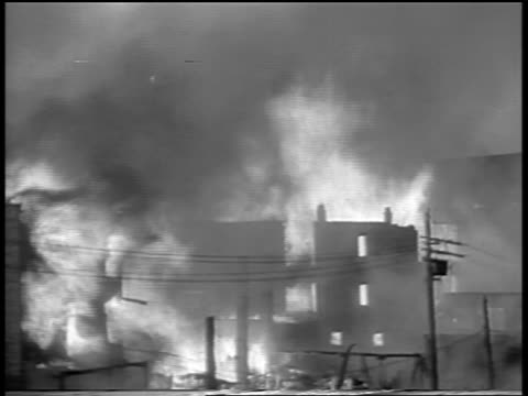 vidéos et rushes de b/w 1934 wide shot buildings telephone poles on fire in chicago stockyard / newsreel - 1934