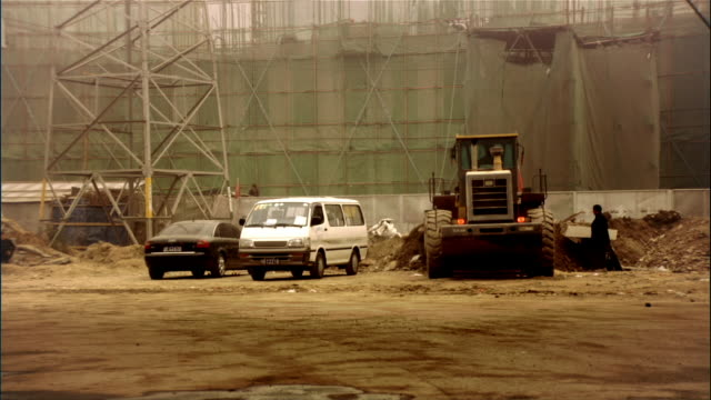 Wide shot bulldozer pushing dirt at construction site/ Beijing, China