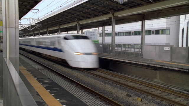 vidéos et rushes de wide shot bullet train speeding through train station / japan - station