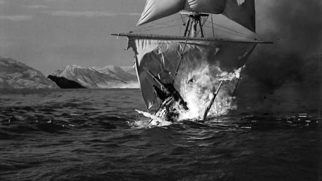B/W wide shot burning sailing ship sinking in ocean with mountains in background