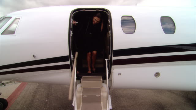 wide shot business couple holding hands and waving while exiting private jet at opa locka airport/ miami, florida, usa - ricchezza video stock e b–roll