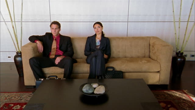 vídeos de stock e filmes b-roll de wide shot businessman and asian businesswoman sitting on office sofa / blonde woman entering + sitting - sentar se