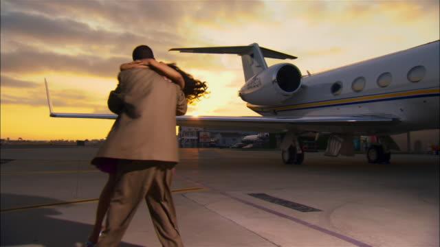 vídeos de stock e filmes b-roll de wide shot businessman and diva embracing on runway near private airplane / long beach, california, usa - só adultos