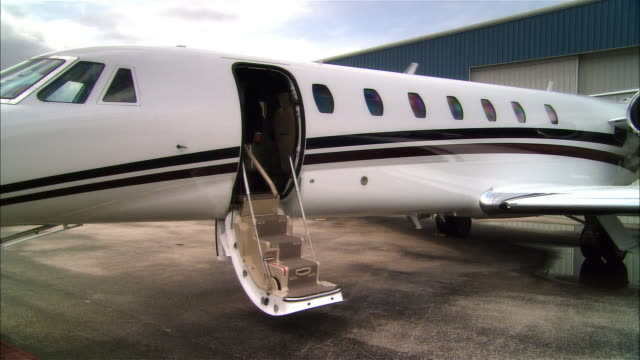 vidéos et rushes de wide shot businessman exiting private jet and waving at opa locka airport/ miami, florida, usa - millionnaire