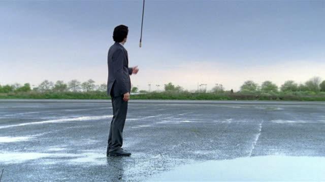 wide shot businessman pulling chain hanging from sky in empty parking lot/ making it rain/ making rain stop - 止まる点の映像素材/bロール