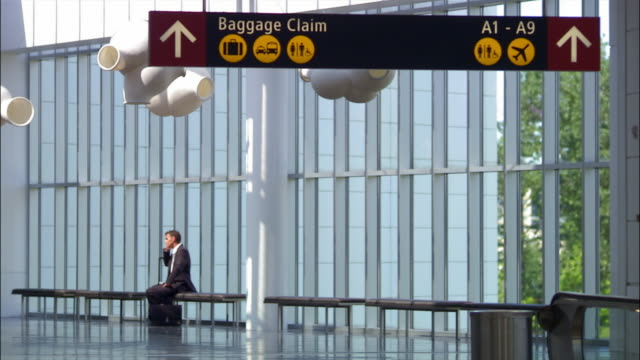 wide shot businessman sitting on bench at airport and talking on mobile phone/ seattle - simbolo informazioni video stock e b–roll