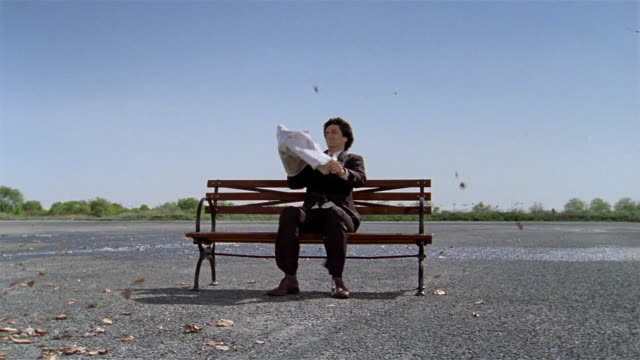 wide shot businessman sitting on bench with newspaper in windstorm / paper blowing away / man running after - ネクタイ点の映像素材/bロール
