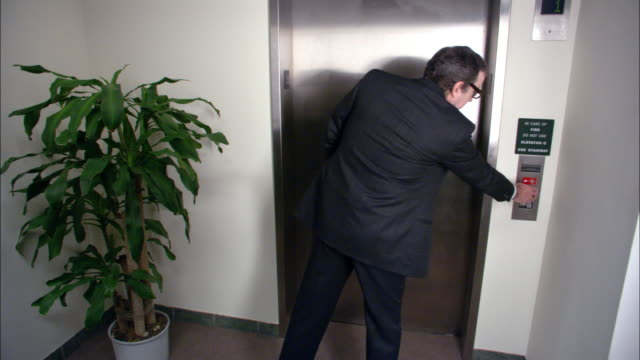 Wide shot businessman waiting for elevator / couple kissing passionately in elevator / door closing / low angle