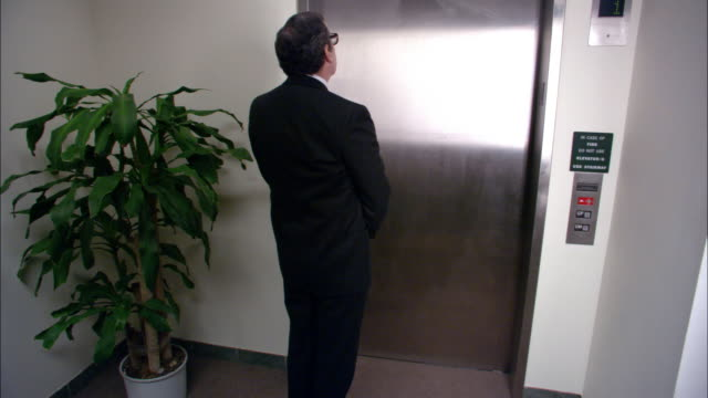 wide shot businessman waiting for elevator / getting into elevator with clown and superhero / los angeles - elastane video stock e b–roll