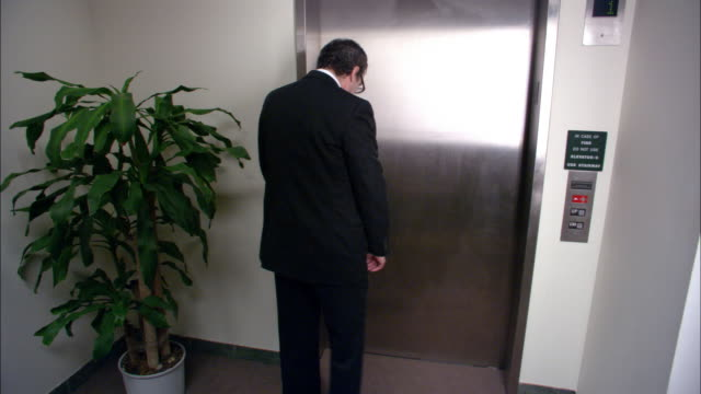 Wide shot businessman waiting for elevator / getting into elevator with clown and superhero / Los Angeles