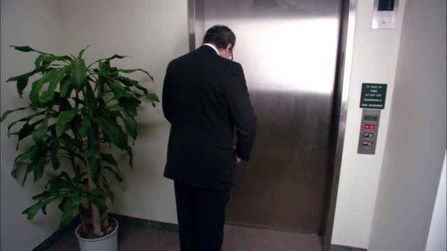Wide shot businessman waiting for elevator/ getting into elevator with clown and superhero/ clown laughing/ low angle
