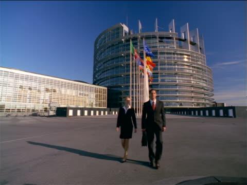 vidéos et rushes de wide shot businessman + woman walking towards camera / eu parliament building in background / strasbourg, france - porte documents