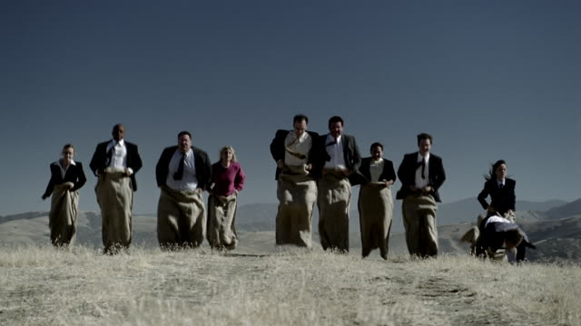 wide shot businesspeople hopping in sack race in field - sack race stock videos & royalty-free footage