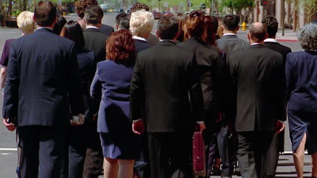 Wide shot businesswoman walking agains flow of crowd on sidewalk / pushing people aside