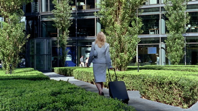 Wide shot businesswoman walking and wheeling suitcase near Sony Centre / Berlin