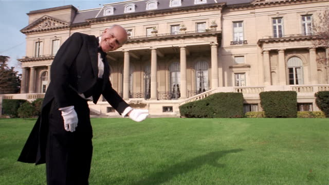 wide shot butler on lawn smiling at cam and extending arm toward mansion in welcoming gesture - millionär stock-videos und b-roll-filmmaterial