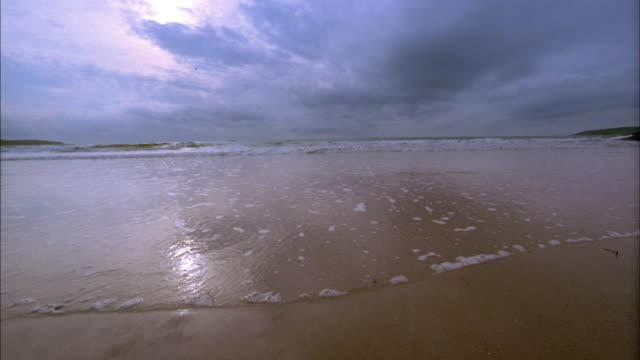 wide shot calm surf rolling into shore on beach / cork, ireland - 2002 stock videos & royalty-free footage
