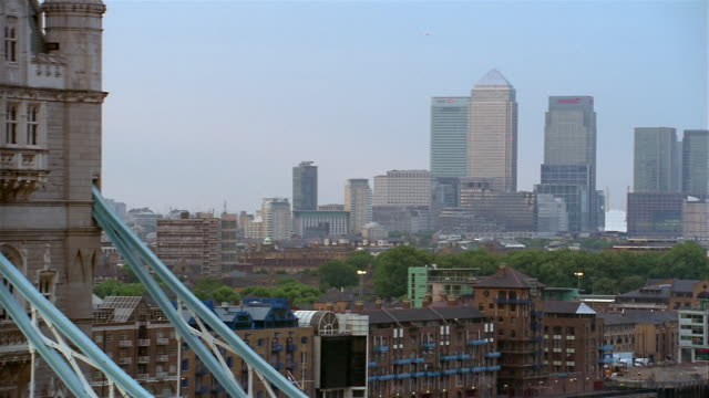 Wide shot Canary Wharf skyline / zoom out pan traffic crossing Tower Bridge over Thames / London