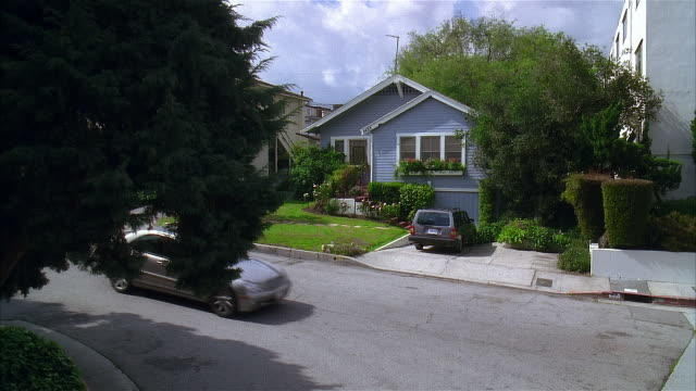 2005 wide shot car driving down street past blue suburban house with car in driveway/ los angeles, california, usa - driveway stock videos & royalty-free footage