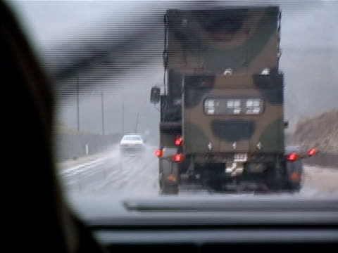 wide shot car driving in rain behind military convoy on wet road/ turkey - moving process plate stock videos & royalty-free footage