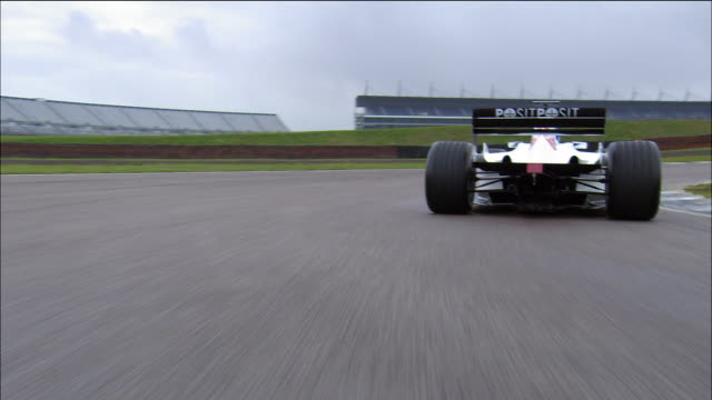 Wide shot car point of view chasing Formula One race car around track