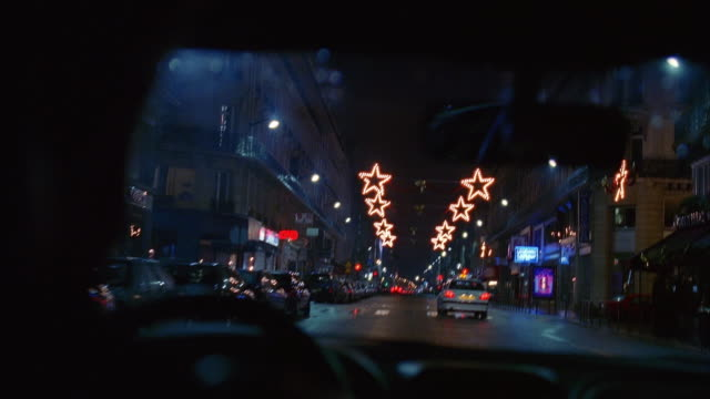 wide shot car point of view commercial street at night with star-shaped christmas lights hanging overhead / paris - car interior stock videos & royalty-free footage