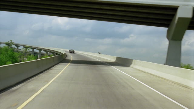 wide shot car point of view driving behind car up highway ramp to overpass to downward ramp - main road stock videos & royalty-free footage