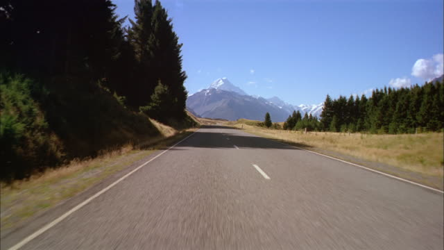 wide shot car point of view driving on left side of empty road with aoraki/mount cook in distance at park / new zealand - car point of view stock videos & royalty-free footage