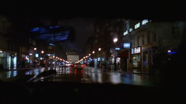 wide shot car point of view driving on street past storefronts at night after rainfall / paris, france - över axel perspektiv bildbanksvideor och videomaterial från bakom kulisserna