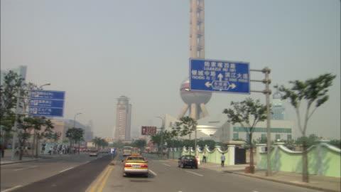 vídeos y material grabado en eventos de stock de wide shot car point of view driving past aquarium with oriental pearl tv tower in background/ shanghai - shanghái