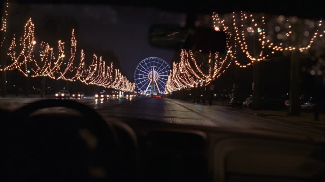 wide shot car point of view street lined with lighted trees with view of ferris wheel and luxor obelisk at night / paris - obelisk of luxor stock videos & royalty-free footage