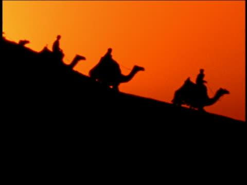 Wide shot caravan of men riding camels down dune in silhouette against orange background / Egypt