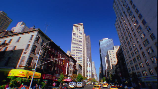 Wide shot car/bus point of view in traffic on city street / skyscrapers in background / Manhattan, New York City