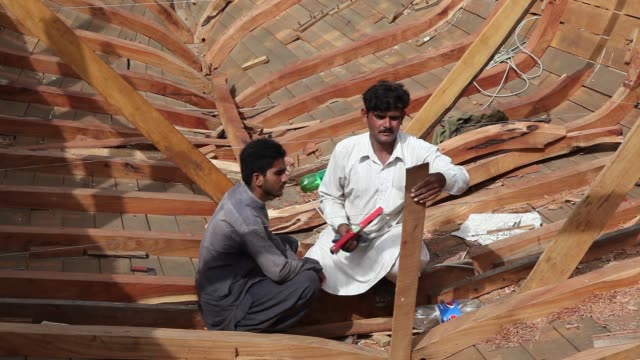 wide shot, carpenters work on the wooden hull of a fishing boat under construction at karachi harbour in karachi, wide shot, a carpenter works on the... - 船体点の映像素材/bロール