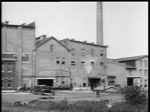 B/W 1927 wide shot cars driving in front of factory / educational