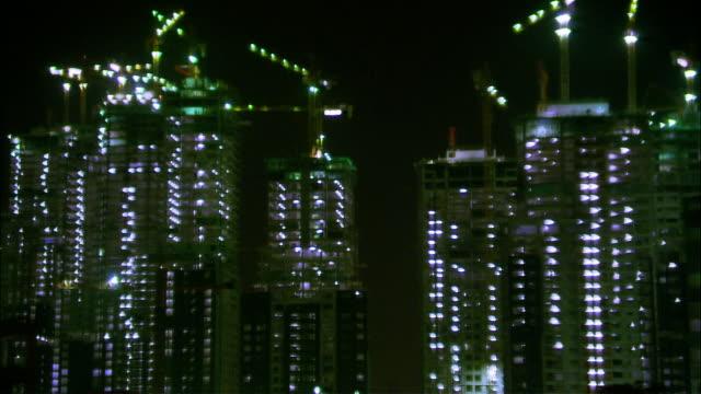 stockvideo's en b-roll-footage met wide shot cars driving past highrise building in burj dubai district/ dubai, united arab emirates - 2007