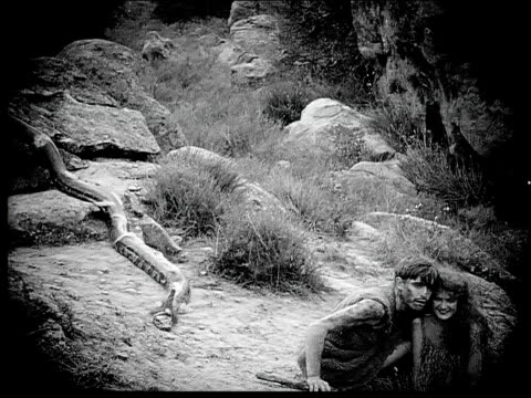 1914 B/W Wide shot Caveman and cavewoman hugging on rocks near snake and running away