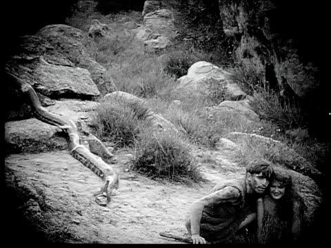 1914 b/w wide shot caveman and cavewoman hugging on rocks near snake and running away - one animal bildbanksvideor och videomaterial från bakom kulisserna