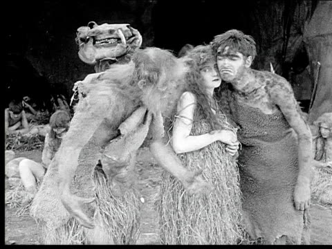 1914 B/W Wide shot Caveman and cavewoman hugging while old caveman talks to them in cave