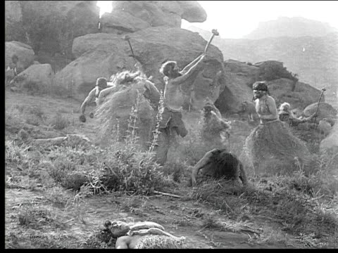 1914 b/w wide shot cavemen and cavewomen celebrating with weapons raised after battle - 1910 stock videos & royalty-free footage