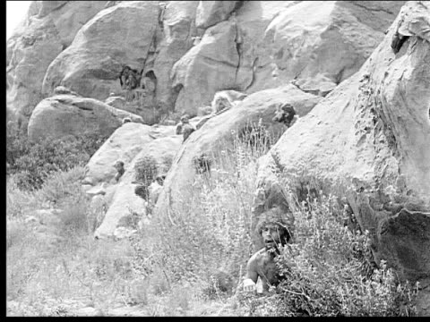 1914 B/W Wide shot Cavemen hiding behind rocks