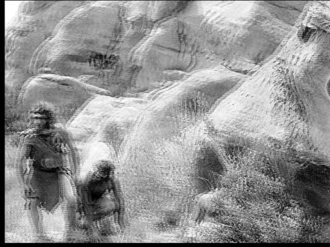 1914 b/w wide shot cavemen running out from behind rocks - evolution stock-videos und b-roll-filmmaterial