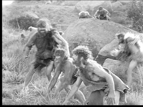 1914 B/W Wide shot Cavemen running out from behind rocks